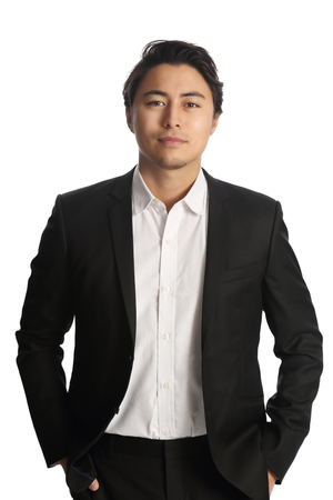 An attractive businessman wearing a black blazer with a white shirt, standing against a white background