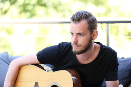 looking away from camera: An attractive man in his 20s wearing a black t shirt, sitting down outside on a summer day with acoustic guitar. Looking away from camera.