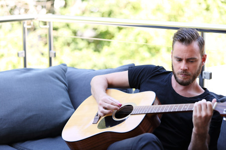 black t shirt: An attractive man in 20s wearing a black t shirt, sitting down outside on a summer day playing his acoustic guitar. Stock Photo