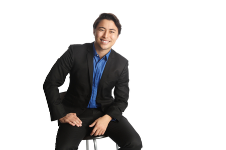 Man in his 20s sitting down on a chair against a white background