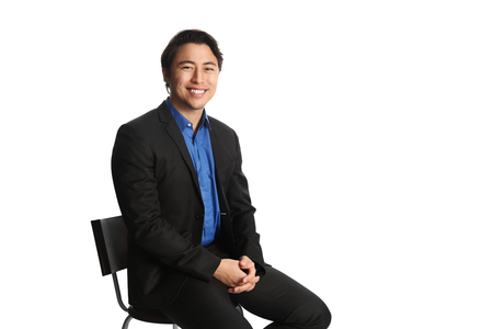 well laid: Man in 20s sitting down on a chair against a white background. Stock Photo