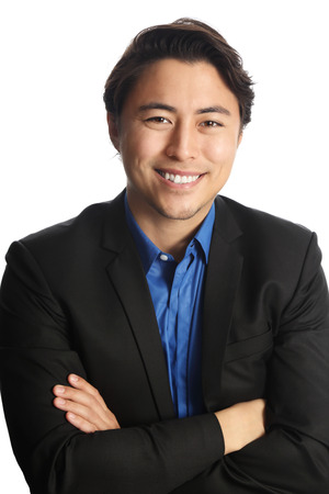 well laid: Man in his 20s sitting down on a chair against a white background, wearing a black suit with a dark blue shirt.