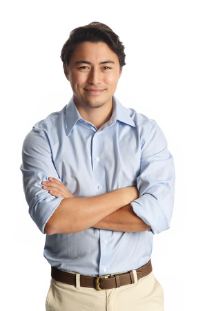 A calm relaxed man wearing a light blue shirt with beige pants, standing against a white background. Carefree and relaxed looking at camera.