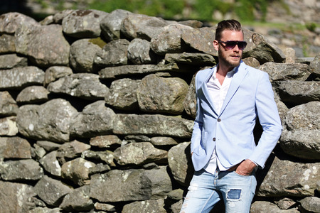 hot guy: An attractive man leaning back against a big wall of rocks, wearing a light blue blazer, sunglasses and jeans, on a sunny summer day.