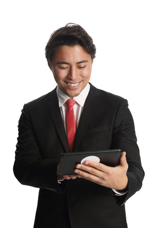 hand held computer: A good looking businessman wearing a black suit, white shirt and a red tie. Holding a digital reader, swiping with his finger. White background. Stock Photo