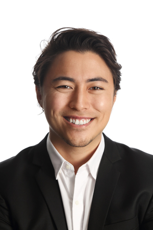 well laid: A young and professional businessman standing in front of a white background smiling looking at camera.