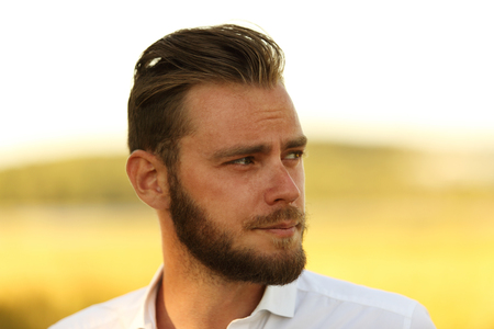 well laid: Man with a beard wearing a white shirt standing in front of a big yellow field with the sun behind, thinking and lonely.