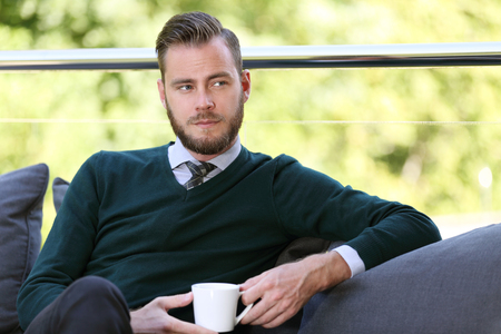 looking away from camera: A businessman wearing a green pullover, shirt and tie. Sitting down outside on a sunny morning with his coffee mug. Looking away from camera.