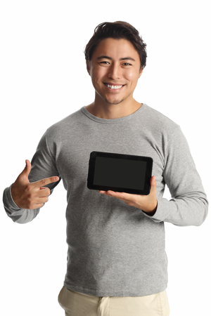 hand held computer: A handsome man in his 20s wearing a grey shirt standing against a white background holding a digital tablet smiling.