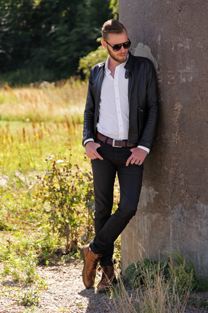 looking away from camera: An attractive man wearing a black jacket and a white shirt and sunglasses, standing leaning against a stone wall on summer day with green grass behind him, looking away from camera. Stock Photo
