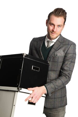 well laid: An attractive businessman in his 20s wearing a grey suit and tie, holding boxes. Standing in front of a white background.