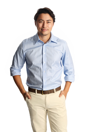 khaki pants: A calm relaxed man wearing a light blue shirt with beige pants, standing against a white background. Carefree and relaxed looking at camera.