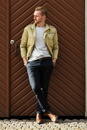 laid back: A fashionable man in his 20s wearing a yellow jacket and dark pants, leaning against a big wooden door outside in a city. Feeling laid back and relaxed.