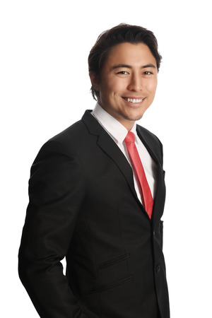 well laid: Smiling businessman looking at camera, wearing a black suit, white shirt and a red tie. Standing in front of a white background. Stock Photo