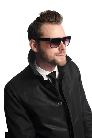 looking away from camera: Portrait of an attractive and trendy man sitting down with a white background, wearing a black jacket, white shirt, black tie and dark sunglasses. Looking away from camera.