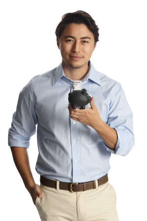 khaki pants: An attractive man in a light blue shirt and khaki pants standing against a white background smiling, holding a black piggy bank with a dollar bill sticking out.