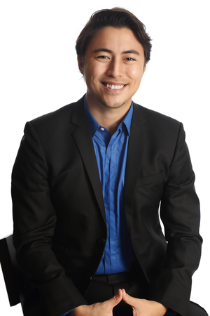 well laid: Man in his 20s sitting down on a chair against a white background, wearing a black suit with a dark blue shirt. Looking at camera with a big toothy smile. Stock Photo