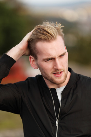 looking away from camera: An attractive man in his 20s wearing a black jacket sitting down outside on a windy autumn day looking away from camera.