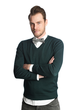 well laid: Trendy and fashionable man wearing a white shirt with a green pullover and bowtie, standing looking at camera in front of a white background.