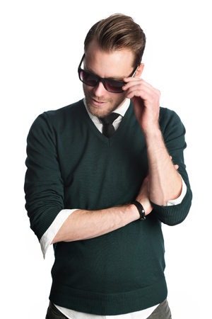 early 30s: A fashionable man in his early 30s standing against a white background wearing a green sweater and jeans with a tie, holding a pair of black sunglasses, smiling and happy.