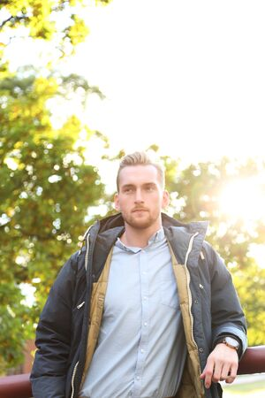 looking away from camera: An attractive blonde man standing leaning outdoors on a sunny day with the sun right behind him, lens flare. Looking away from camera. Stock Photo