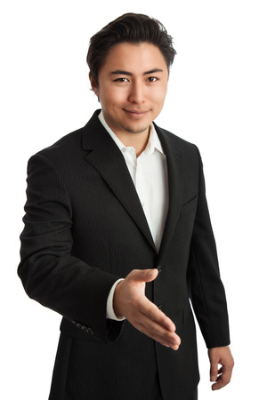well laid: Smiling casual dressed businessman stretching out his hand for a handshake, looking at camera. White background. Stock Photo