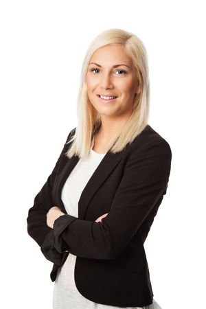 An attractive blonde businesswoman standing in front of a white background smiling towards camera.