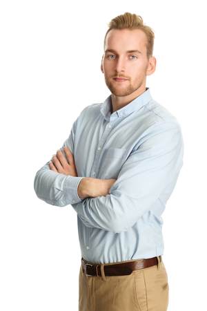 well laid: A handsome man in his 20s standing against a white background, wearing a blue shirt tucked in to his khaki pants. Smiling towards camera.