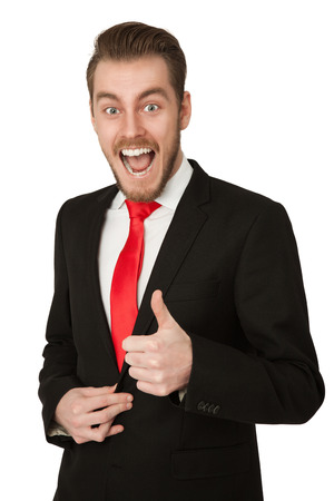 lunatic: Crazy looking businessman screaming and doing thumbs up, wearing a black suit and red tie. White background.