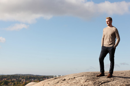 high up: A handsome blonde man wearing a beige pullover shirt, standing high up on a mountain overlooking the city below. Sunny summer day. Stock Photo