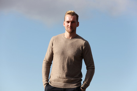 well laid: A handsome blonde man wearing a beige pullover shirt, standing high up on a mountain overlooking the city below. Sunny summer day. Stock Photo