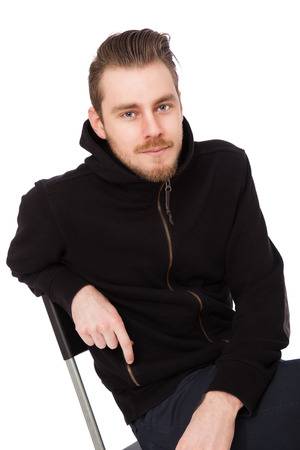 tough man: Focused tough man wearing a black hoodie sitting down on a chair staring at camera. White background. Stock Photo