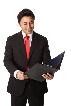 Handsome businessman in a black suit with a red tie, holding a folder reading from a document. White background.