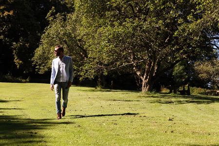 A man wearing a blazer, sunglasses and jeans walking on a big field of grass on a sunny day in the middle of summer.