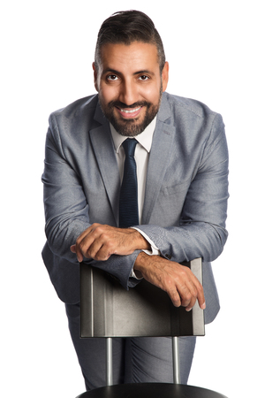 well laid: A mature businessman in his 40s wearing a grey suit with a blue tie, sitting down on a chair looking at camera. White background. Stock Photo
