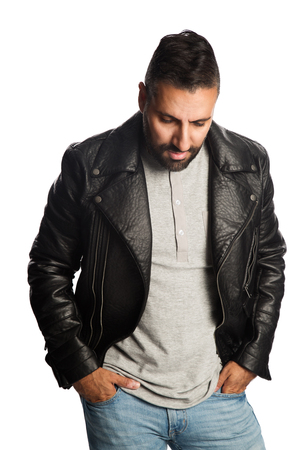 Trendy man standing against a white background wearing a black jacket and jeans, feeling relaxed and comfortable. Imagens
