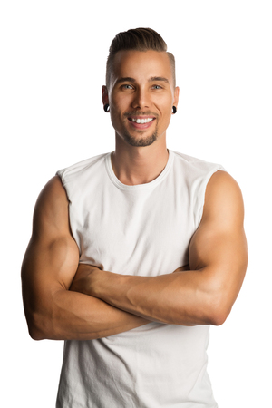 Well trained and attractive man wearing a white tank top standing against a white background with his arms crossed. 写真素材