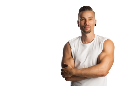 Well trained and attractive man wearing a white tank top standing against a white background with his arms crossed.