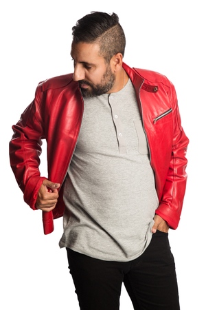 Trendy man in a red leather jacket and jeans, standing against a white background looking at camera. Stockfoto