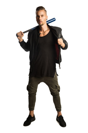 Tough macho man wearing a black leather jacket, standing against a white background with a baseball bat looking at camera.