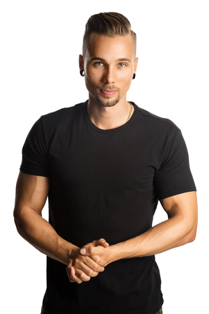 A fit attractive man wearing a black t-shirt, with arms crossed looking at camera. White background. Imagens