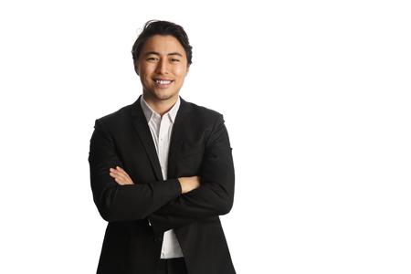 Un atractivo hombre de negocios vistiendo un blazer negro con una camisa blanca, de pie sobre un fondo blanco mirando a la cámara. Sonríe en su rostro.