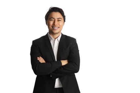 Un homme d'affaires séduisant portant un blazer noir avec une chemise blanche, debout sur un fond blanc regardant la caméra. Sourire sur son visage.