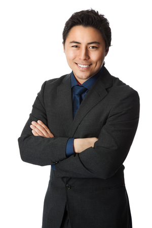 A handsome businessman wearing a grey suit with a blue shirt and tie standing against a white background. Banque d'images