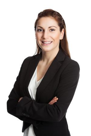 Eine attraktive brünette Geschäftsfrau, die einen schwarzen Anzug und ein weißes Hemd trägt und mit ihren Armen vor weißem Hintergrund verschränkt steht.