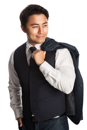 Attractive well dressed businessman wearing a white shirt, vest and tie, with his jacket over his shoulder standing against a white background smiling.