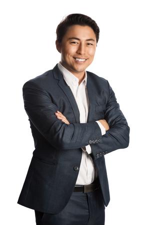 Ein gut gekleideter Geschäftsmann in blauem Anzug und weißem Hemd, der vor einem weißen Hintergrund steht und in Richtung Kamera lächelt. Standard-Bild