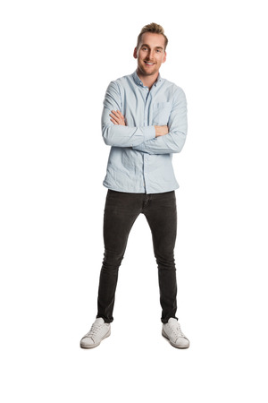 A handsome man in his 20s standing against a white background, smiling, wearing a blue shirt and grey jeans. Imagens