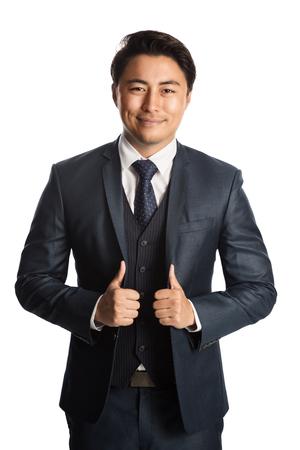 Homme d'affaires beau et bien habillé dans un costume, une cravate et un gilet, debout sur un fond blanc souriant vers la caméra.