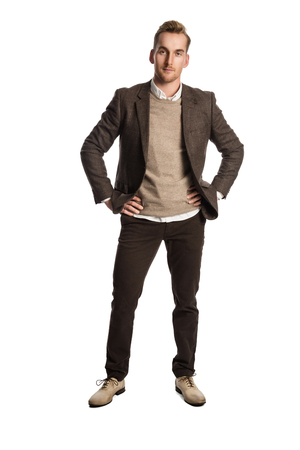 A attractive man in his 20s standing against a white background wearing a brown suit with a sweater and white shirt. Stock Photo